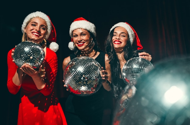 Bonne année à toi! trois belles femmes sexy en bonnets de noel avec des boules disco dans leurs mains. fête du nouvel an. la veille de noël.