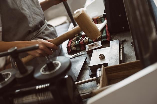 Une bonne balle. gros plan sur une femme joaillière faisant une bague en argent à l'aide d'un marteau dans son atelier.