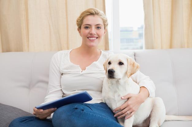 Bonne blonde à l'aide de tablet pc avec chiot