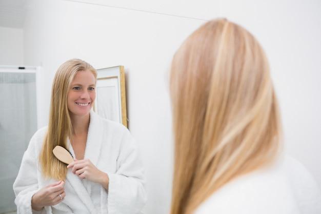 Bonne blonde se brosser les cheveux