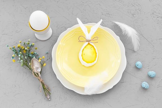 Bonne branche de pâques ou petit-déjeuner. sur des assiettes à surface grise avec œuf coloré et décorations.