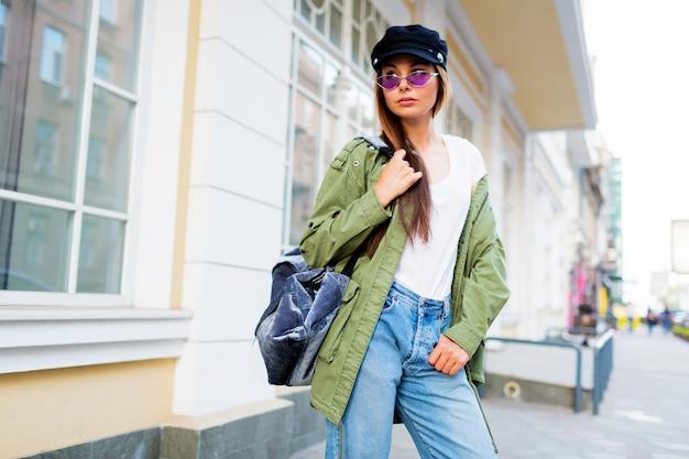Bonne brune weoman posant en plein air. chapeau élégant, lunettes de soleil et veste verte.
