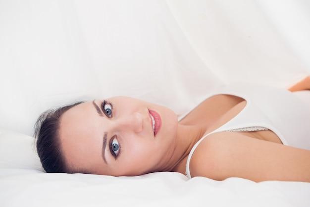 Bonne brunette allongée sous les draps à la recherche
