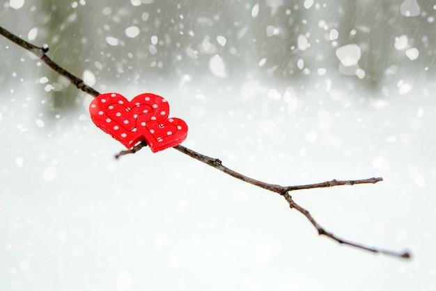 Bonne carte de voeux ou bannière de la saint-valentin. coeurs rouges sur une branche d'un arbre couvert de neige en hiver. vacances joyeuse saint-valentin. chutes de neige sur le fond de la forêt