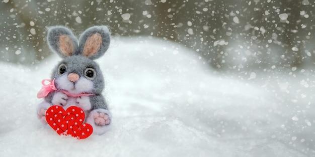 Bonne carte de voeux ou bannière de la saint-valentin. lapin en peluche tenant un coeur rouge ka symbole de l'amour. vacances joyeuse saint-valentin. chutes de neige sur le fond de la forêt