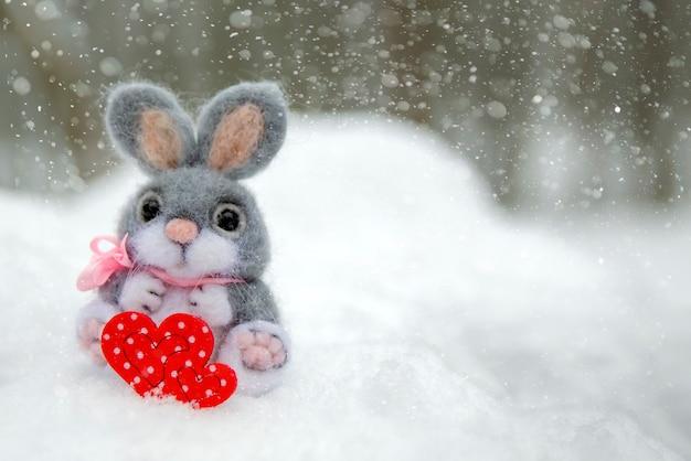 Bonne carte de voeux ou bannière de la saint-valentin. lapin en peluche tenant un coeur rouge symbole de l'amour. vacances joyeuse saint-valentin. chutes de neige sur le fond de la forêt.