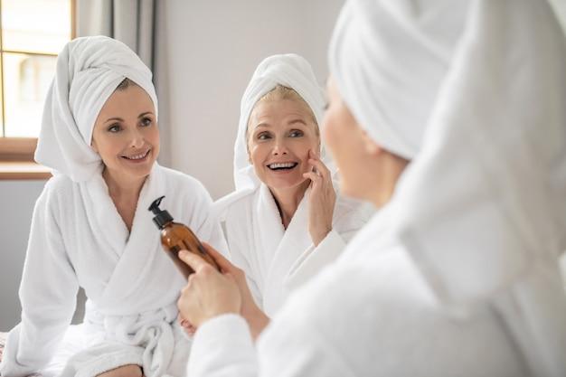 Bonne compo. trois femmes adultes attentives en blouses blanches et serviettes sur la tête étudiant la composition d'un produit cosmétique se reposant dans une pièce lumineuse