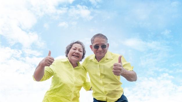 Une bonne confiance des seniors asiatiques en bonne santé recommande de partir en vacances ensemble sur un ciel clair avec une chemise colorée