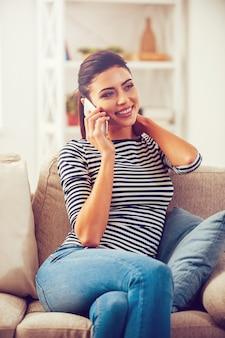 Bonne conversation avec un ami. belle jeune femme parlant au téléphone portable et souriant