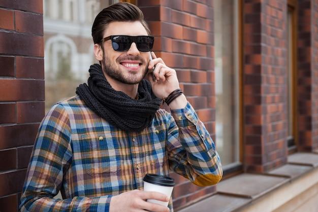 Bonne conversation avec un ami. gai jeune homme tenant une tasse de café et parlant au téléphone portable tout en se tenant dans la rue