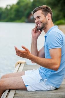Bonne conversation avec un ami. vue latérale du beau jeune homme parlant au téléphone portable et souriant alors qu'il était assis au bord de la rivière