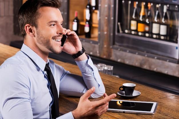 Bonne conversation avec un ami. vue latérale d'un jeune homme heureux en chemise et cravate parlant au téléphone portable et faisant des gestes assis au comptoir du bar