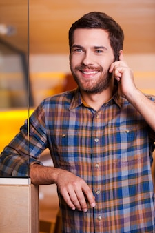 Bonne conversation. beau jeune homme parlant au téléphone portable et souriant en se tenant debout à l'intérieur