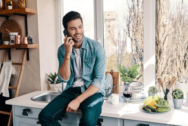 Bonne conversation. beau jeune homme en tenue décontractée parlant au téléphone alors qu'il était assis dans la cuisine à la maison