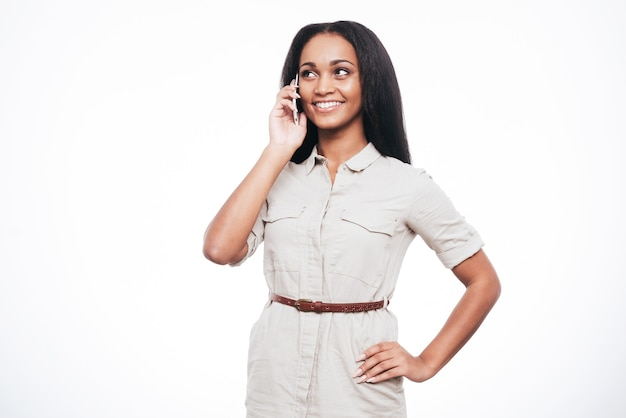 Bonne conversation. belle jeune femme africaine parlant au téléphone portable et souriant en se tenant debout sur fond blanc