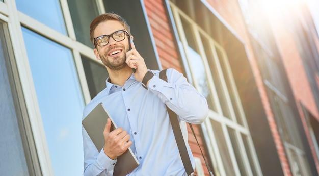 Bonne conversation jeune homme d'affaires caucasien heureux portant une chemise bleue et des lunettes tenant son ordinateur portable