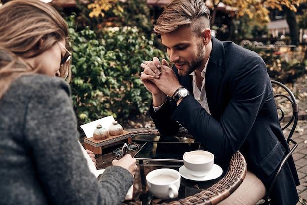 Bonne discussion d'affaires. beau jeune homme en vêtements décontractés intelligents souriant tout en discutant avec une jeune femme au restaurant