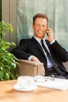 Bonne discussion d'affaires. homme mûr gai en tenues de soirée parlant au téléphone portable et souriant assis à la chaise à l'extérieur avec une tasse de café au premier plan