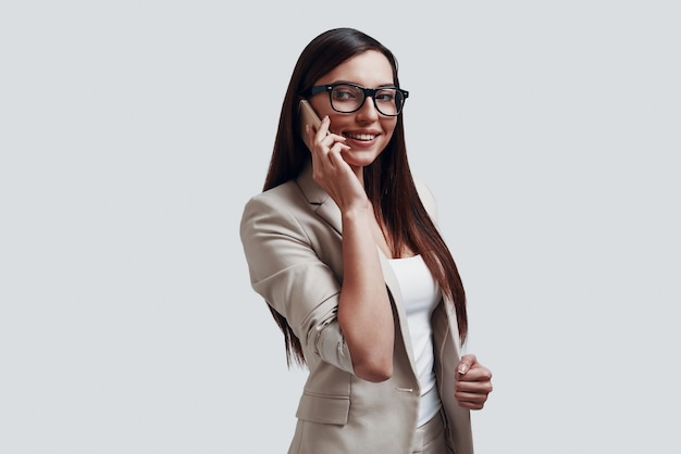 Bonne discussion d'affaires. jolie jeune femme parlant au téléphone et souriant en se tenant debout sur fond gris