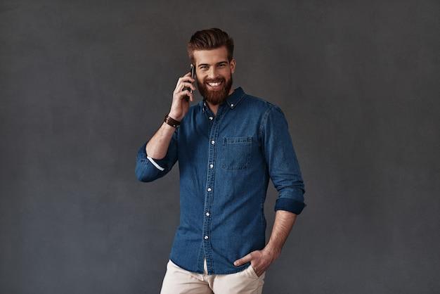 Bonne discussion avec ma copine. beau jeune homme parlant au téléphone intelligent et regardant la caméra en se tenant debout sur fond gris