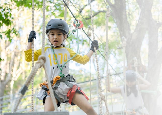 Bonne écolière bénéficiant d'activité dans un parc d'aventure