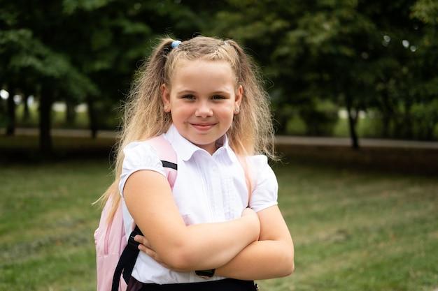 Bonne écolière bouclée blonde en uniforme scolaire avec sac à dos rose retour à l'école en plein air.