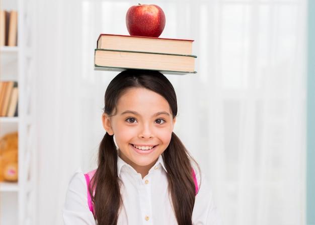 Bonne écolière avec des livres et pomme sur la tête