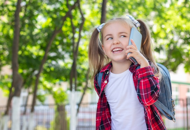 Bonne écolière avec un sac à dos, parler au téléphone dans la rue. dans un t-shirt blanc et une chemise à carreaux