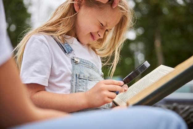 Bonne écolière souriante tenant une loupe à la main alors qu'elle était assise à l'extérieur