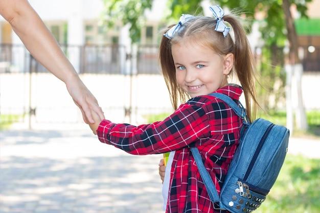 Bonne écolière tient la main de maman et va à l'école. dans un t-shirt blanc et une chemise à carreaux