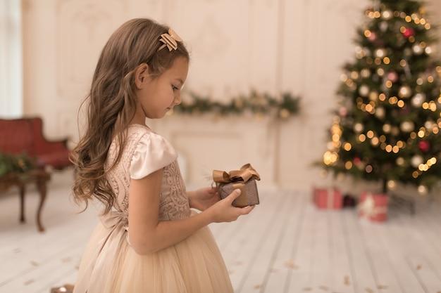 Bonne enfance, conte de noël magique. petite princesse avec le cadeau du père noël pour noël.
