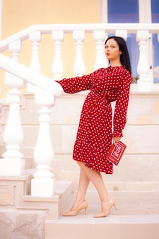 Bonne épicerie. portrait d'une belle femme blanche traditionnelle en robe rouge tenant un sac en papier rempli d'épicerie.