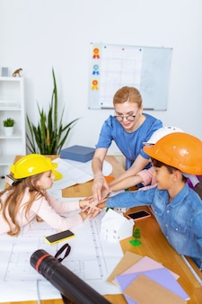 Bonne équipe. enseignant et élèves appréciant de travailler en grande équipe après avoir modélisé une ville intelligente