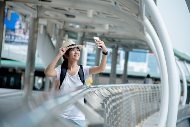 Bonne étudiante asiatique souriante avec sac à dos au fond de la ville