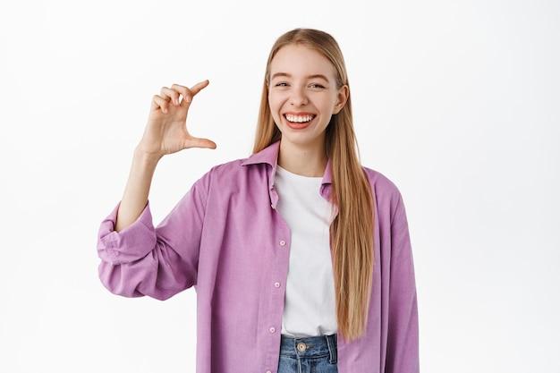 Bonne étudiante blonde montrant une petite taille, un petit geste de la main et souriant gai, debout dans des vêtements décontractés contre un mur blanc