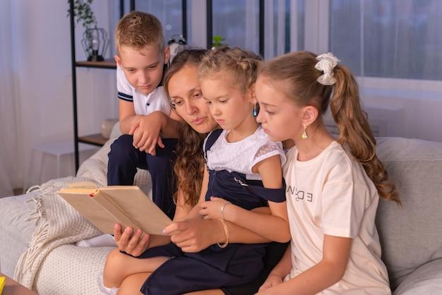 Bonne famille jeune maman nounou lisant un livre racontant aux petits enfants un drôle de conte de fées assis