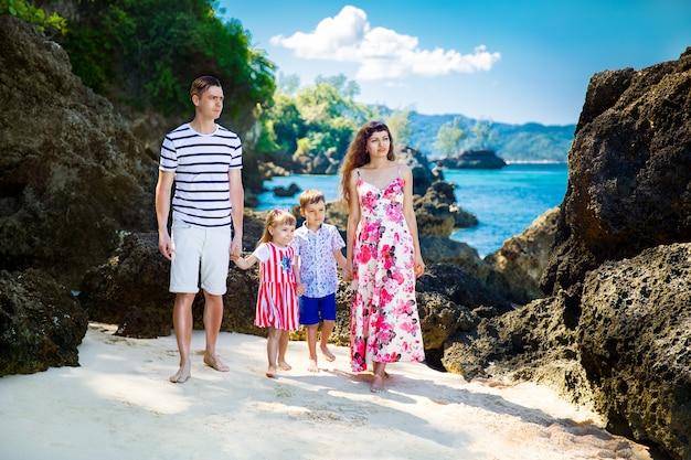 Bonne famille maman papa fille et fils marchent sur une plage tropicale pendant les vacances d'été