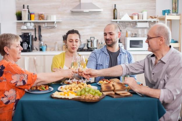 Bonne famille multigénérationnelle trinquant à vin pendant le déjeuner. savoureuses pommes de terre assaisonnées maison. parents âgés et enfants plus âgés.