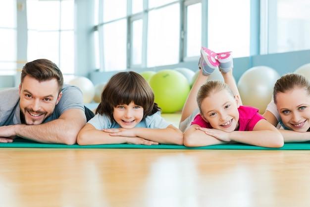Bonne famille sportive. famille heureuse se liant les uns aux autres en position allongée sur un tapis d'exercice dans un club de sport