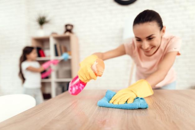 Bonne femme applique un vernis pour les meubles sur la table.