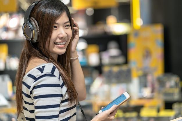 Bonne femme asiatique écoute et technologie de test ecouteur ou casque dans un magasin de magasin