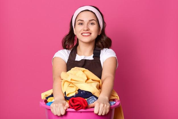 Bonne femme au foyer à la recherche de standing isolé sur rose en studio, souriant sincèrement