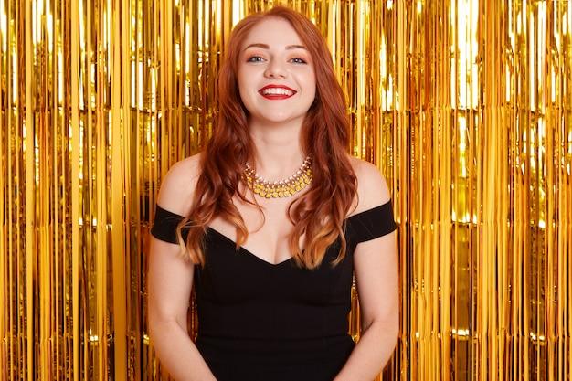 Bonne femme aux cheveux rd avec des lèvres brillantes portant une robe noire et un collier posant isolé sur le mur avec des guirlandes d'or, regarde en souriant directement à la caméra