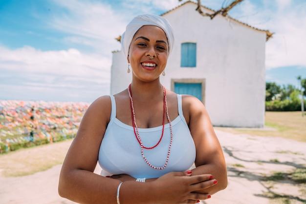 Bonne femme brésilienne habillée en costume traditionnel bahianais, les bras croisés dans le centre historique de porto seguro en arrière-plan