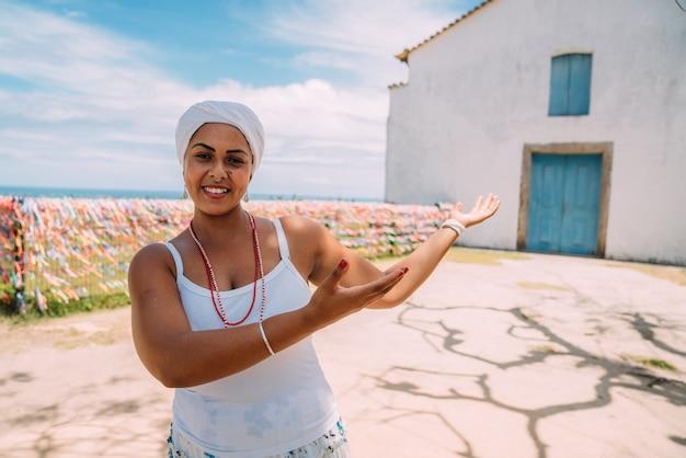 Bonne femme brésilienne habillée en costume traditionnel bahianais montrant quelque chose sur la paume de sa main, regarde la caméra, avec le centre historique de porto seguro en arrière-plan