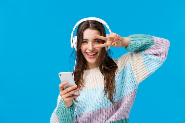 Bonne femme brune impertinente dans les écouteurs, pull d'hiver, appréciant les chansons préférées dans les nouveaux écouteurs, montre la paix, geste disco tenant le smartphone, caméra souriante heureuse