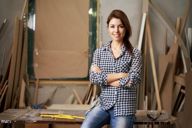 Bonne femme charpentier en chemise à carreaux avec les bras croisés en atelier