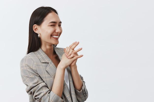 Bonne femme joyeuse riant de joie et d'enthousiasme, debout à moitié retourné sur un mur gris, joignant les mains, regardant à droite