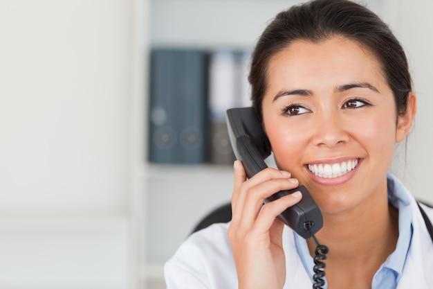 Bonne femme médecin au téléphone et posant