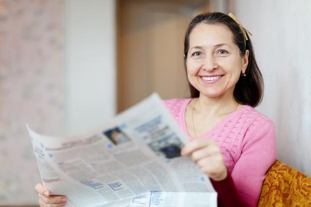Bonne femme mûre appréciant avec le journal